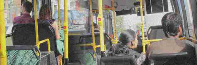 couples riding in a bus, viewed from behind