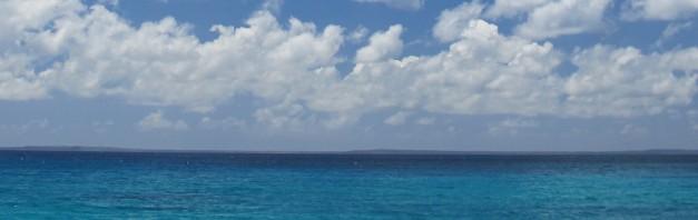 White fluffy clouds, blue sky and light blue sea gradually turning dark blue toward the horizon.