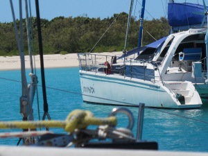 Ropes and rigging, light blue water, white yachtfacing white sand beach and green vegetation