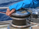Hand in blue waterproof gripping a large yacht winch