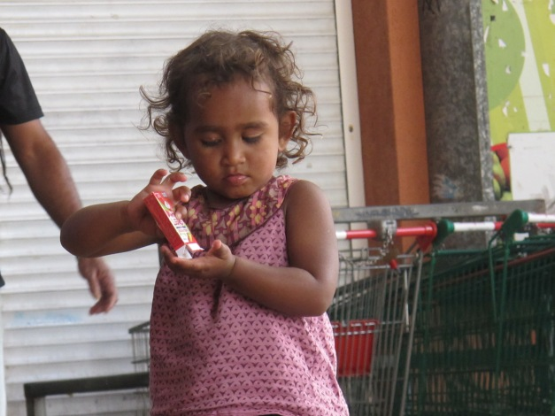Kanak or mixed race toddler shakes sweet packet into hand