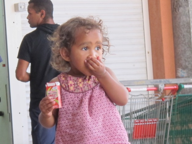 Mixed race / kanak toddler puts her hand to her mouth, having extracted a sweet from the packet