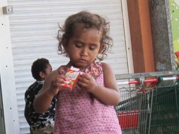 a kanak toddler in a pink dress opens a cardboard packet of sweets