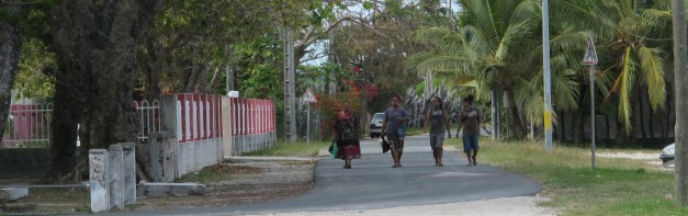 four Kanak women walking abreast on sealed road - coconut trees and flame trees around them