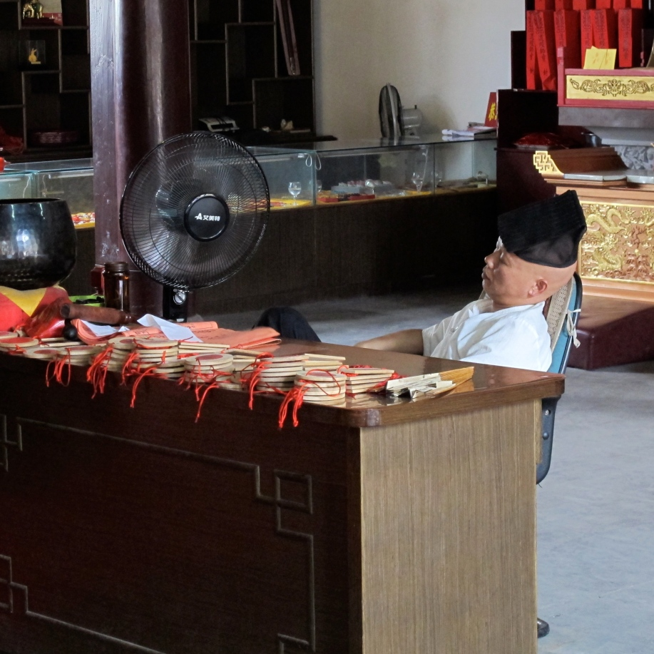 A temple priest sits dozing behind a crowded desk while an electric fan blows air.