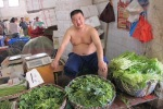 A bare chested man sits behind his baskets of green vegetables