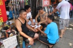 Three men play cards on a low table outside a shoe stall, while a fourth looks for potential customers.