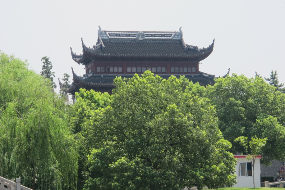 A Chinese tower with the traditional curves eaves, is screen by tall leafy trees.