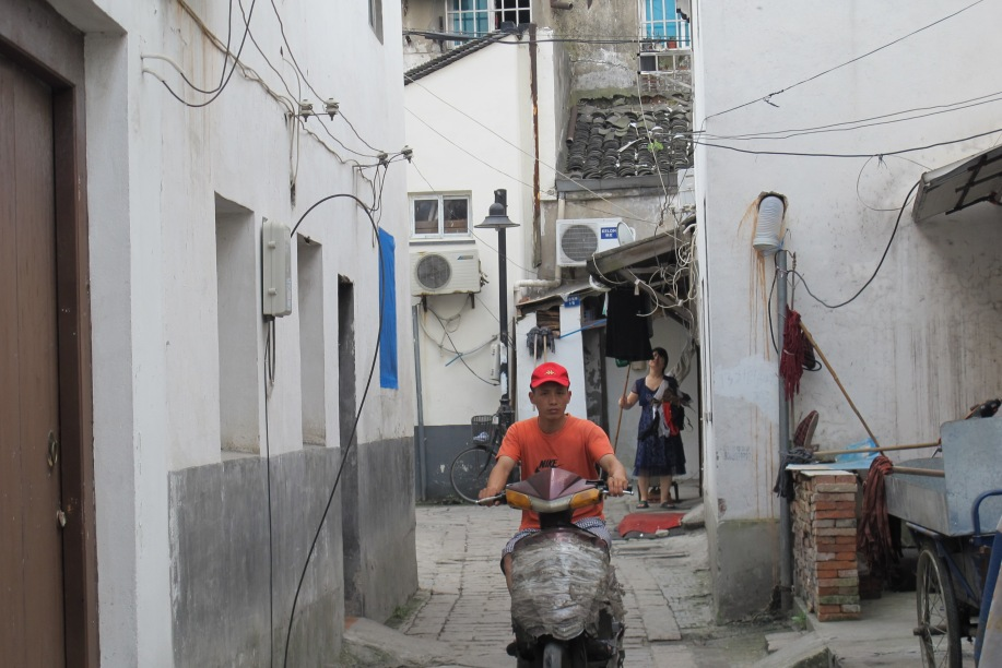 a man dressed in red, riding a grey moped, drives toward the camera between the walls of a narrow lane.