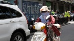 A person riding a moped is totatly covered by cloth in an apparent effort to avoid dust and exhaust fumes.