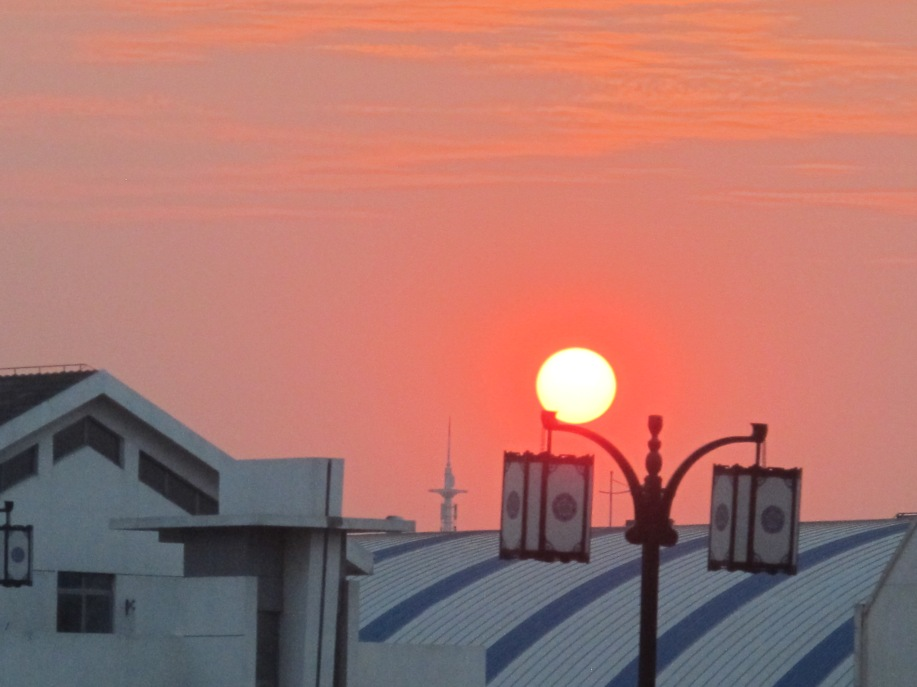 A white sun hovers over rooftops and lanterns as it sinks toward evening in a red sky.