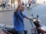 A moped rider in a blue shirt cheerfully waves at the camera