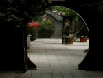 a tiled formal garden is glimpsed through a round moon gate.