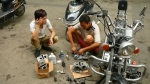 two men are surrounded by a disassembled motorbike and parts