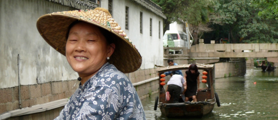 Women in straw hat, a small shallow draft boat behind her.