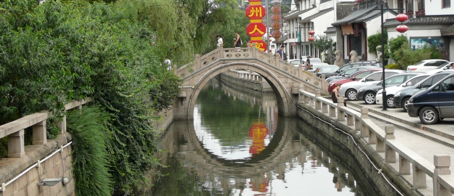 Reflection of an arched bridge in a still canal creates the illusion of a circle in the water.