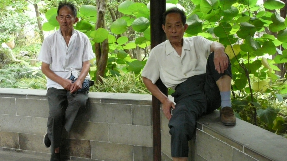 two men sitting on a low wall, surrounded by greenery