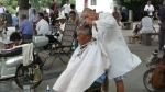 surrounded by pushbikes, mopeds, pediestrians, a barbers trims the hair of a sheet draped client