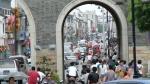 a crowd of pedestrians walking through the arch through a thick, tall wall.