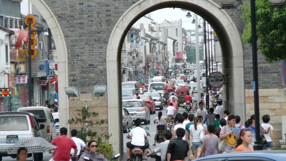 a crowd of pedestrians walking through the arch through a thick, tall wall.