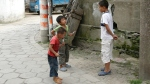 An older boy confronts two younger children eating ice blocks