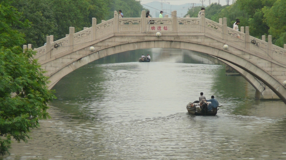 a small boat creating a v shaped wake travels under an ornate arched bridge.