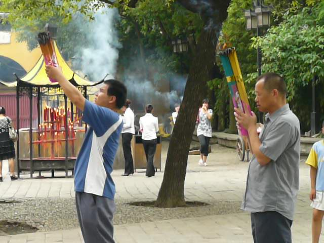 Two men offer large bundles of burning incense in a prayerful offering outside a temple
