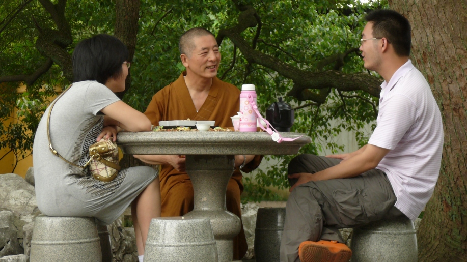 flanked by a young woman and a young man, a brown robed monks converses with his companions . A flask of tea and snaks sit on a table before them.