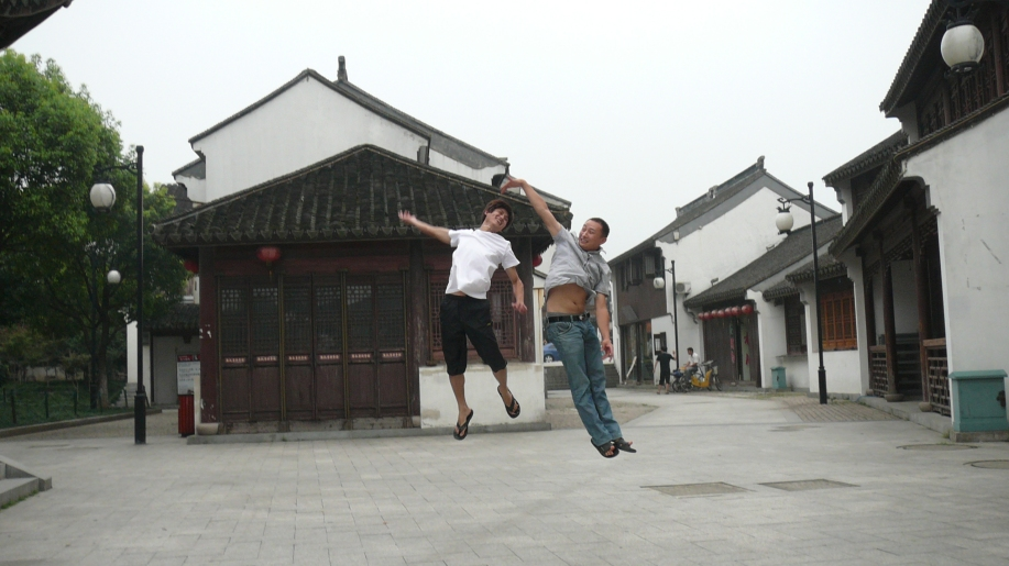 two young men jumping in the air surrounded by houses